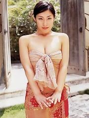 Erotic asian beauty laying around on the beach in her bikini