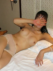 Asian amateur wife gets naked and shows her large hairy pussy